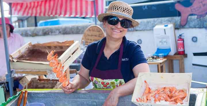 Stallholder at Streatham Food Festival holding a skewer of prawns