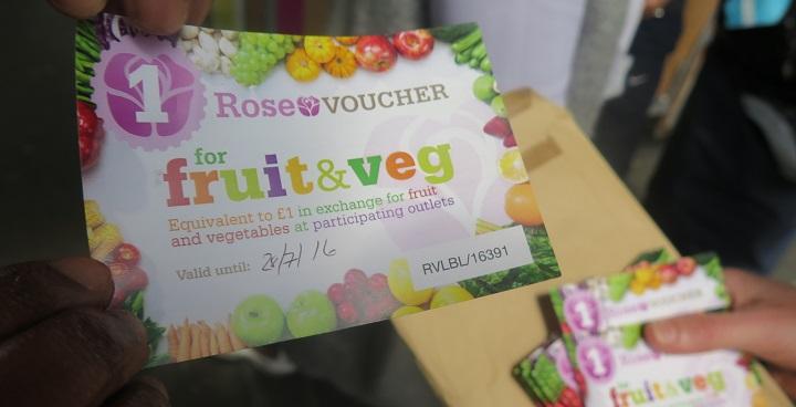 A hand holding a Rose voucher