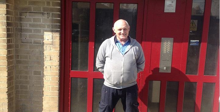 Stephen in grey hoodie and blue shirt outside red communal doors of Dan Bryant House