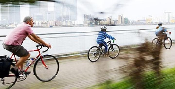 Family cycling alongside the Thames