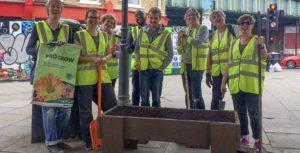 group of 6 volunteers in hi-viz ytellow vests lean on spoades to rest after filling planters with compost outside Herne Hill Station