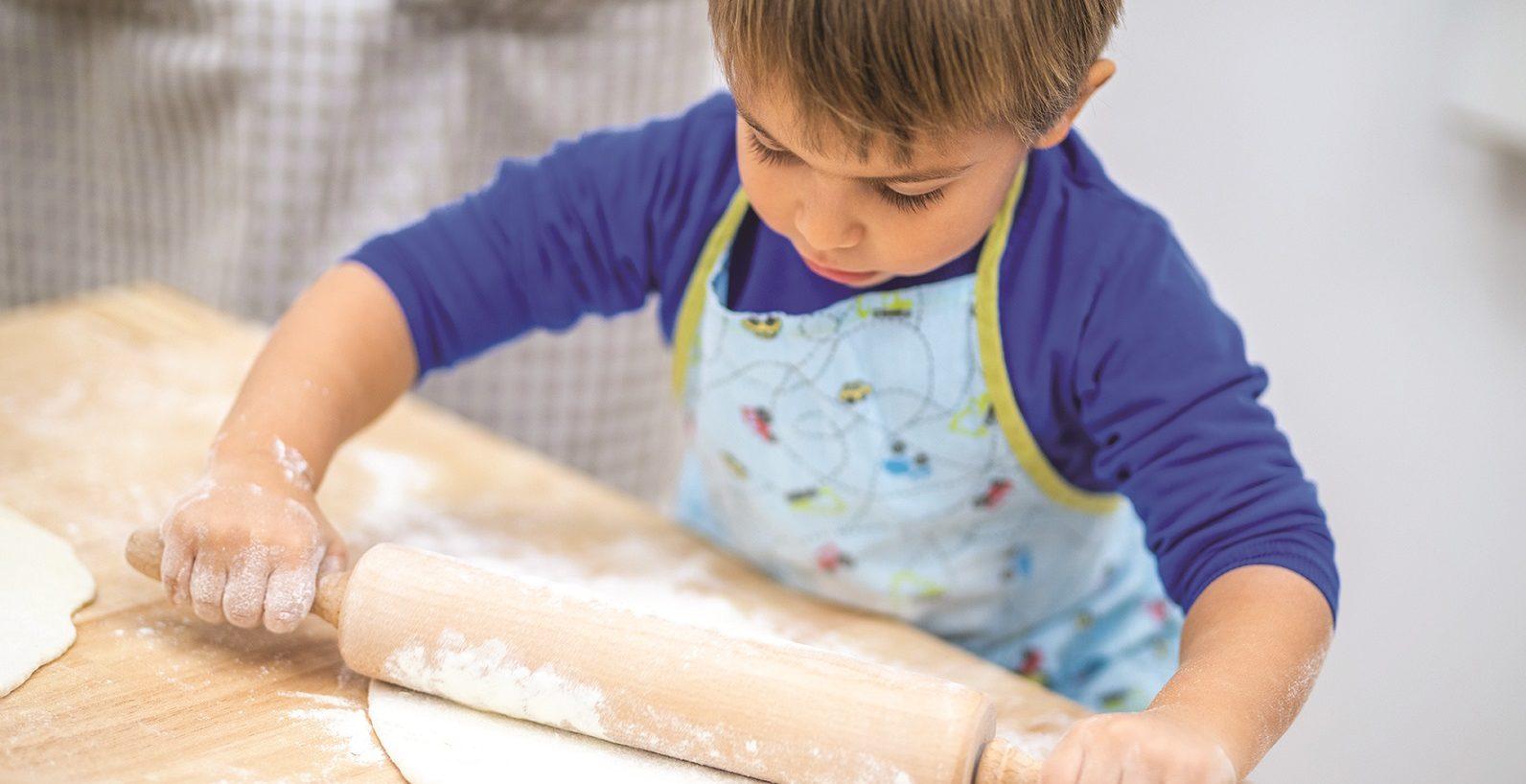 Little boy rolling dough