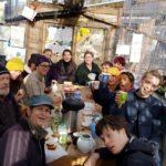 Group of men and women raise mugs in 'cheers' gesture